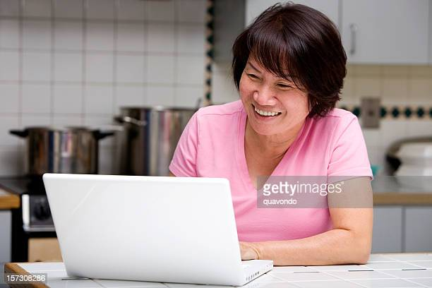 Asian Adult Woman Laughing and Smiling, Using Laptop in Kitchen