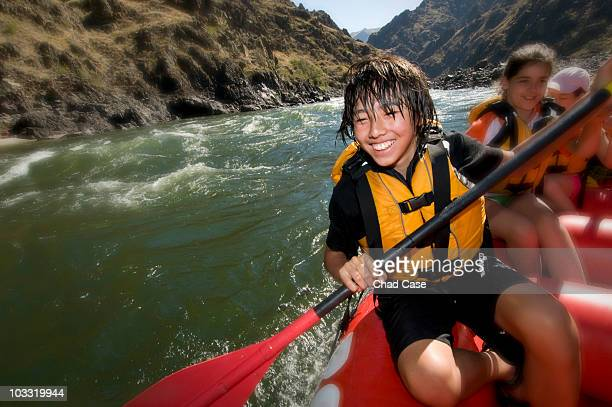 Asian American boy smiling while white water rafting.