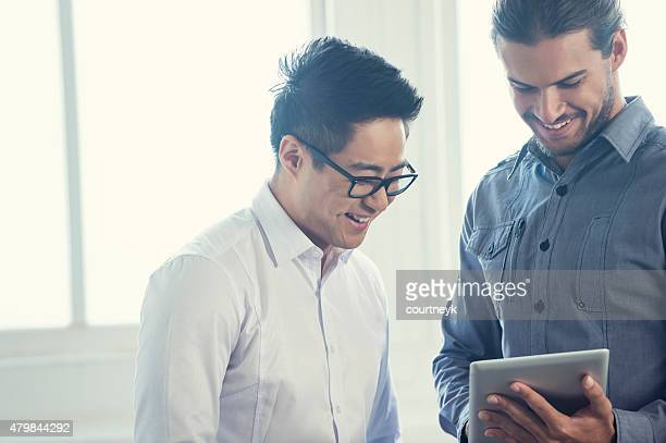 Asian and Caucasian businessmen working on digital tablet.