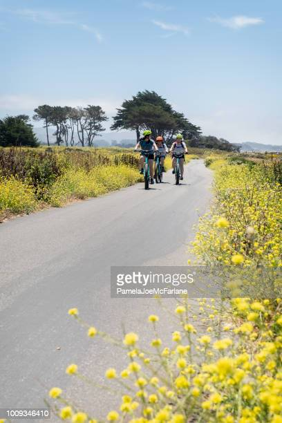 asian and mixed ethnic women biking along path of wildflowers - san mateo county stock pictures, royalty-free photos & images