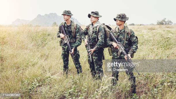 asian army soldiers with guns during the military operation in the field, war concept - army training stock pictures, royalty-free photos & images