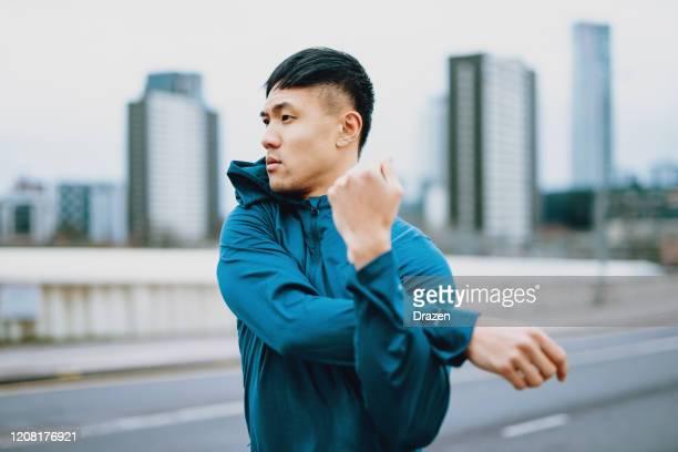 asiatischer sportler dehnt sich und joggt an bewölktem tag - aktiver lebensstil stock-fotos und bilder
