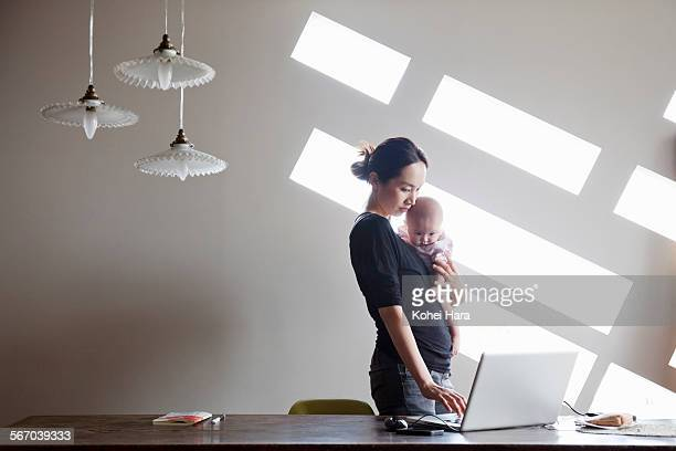Asian baby and beautiful mother working at home