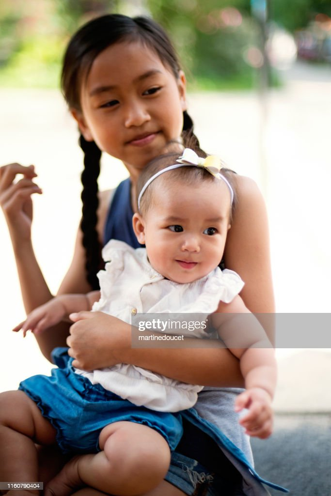 Asian baby girl with big sister on restaurant terrace. : Stock Photo