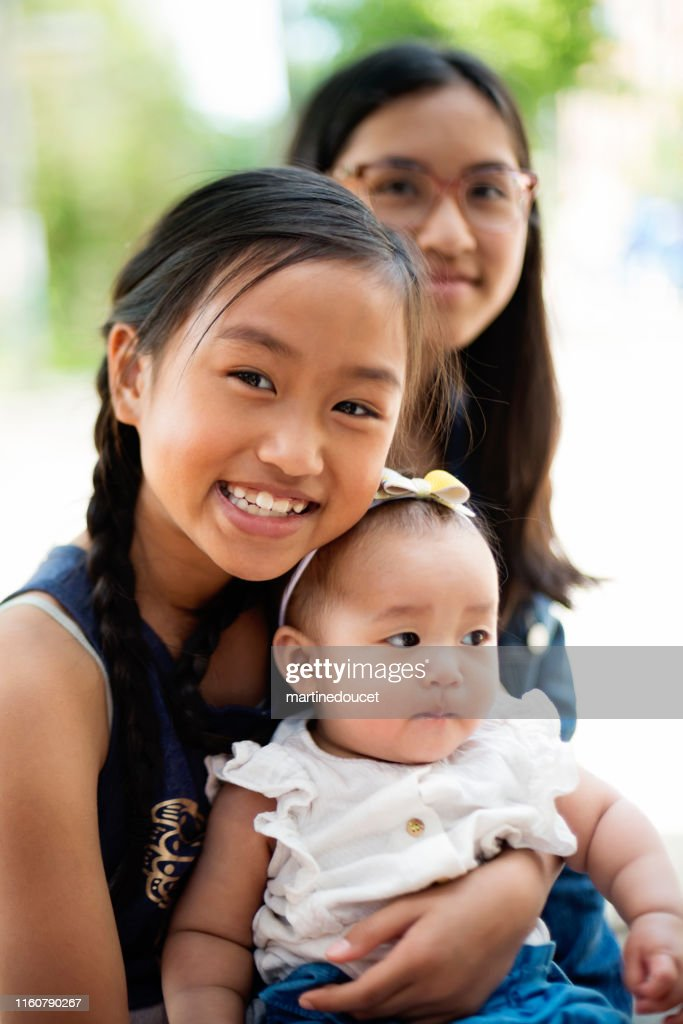 Asian baby girl with big sisters on restaurant terrace. : Stock Photo