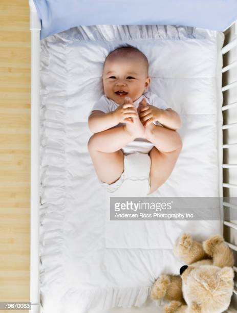 Asian baby laying in crib
