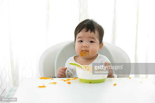 asian baby learning self feeding. - pureed stock photos and pictures