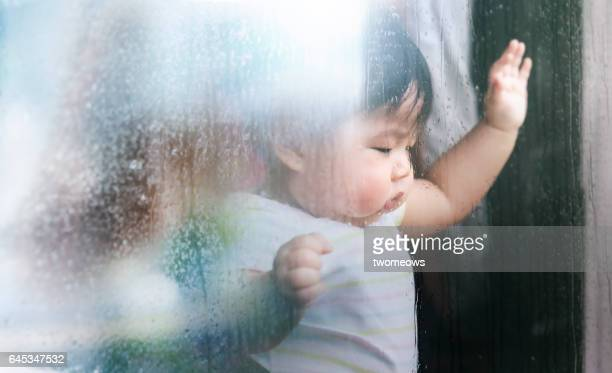 Asian baby looking sad in rainy day.