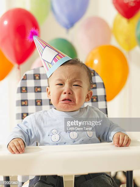 Asian baby wearing party hat and crying in high chair