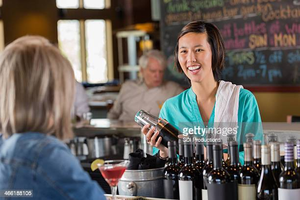 Asian bartender making mixed drink while talking to restaurant customer