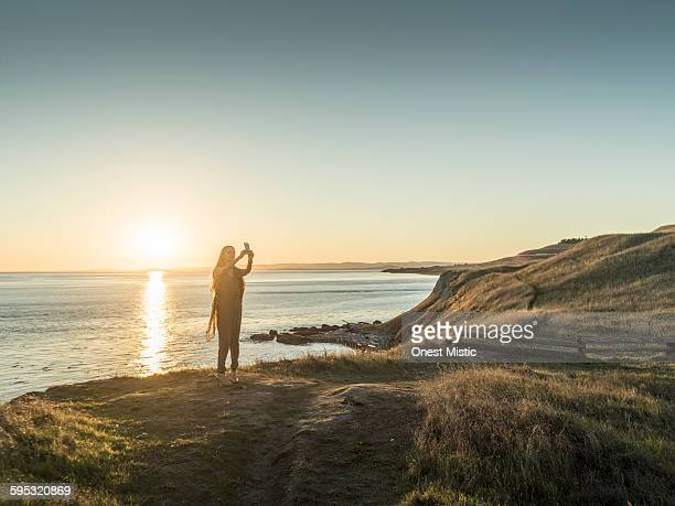 asian beautiful woman taking  picture at cliff
