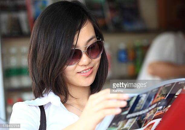 Asian beauty holding a magazine at the newsstand