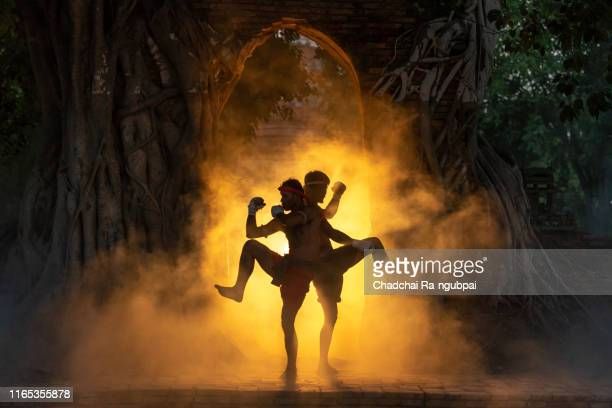 asian boxers are fighting muay thai martial arts at thai temples. muay thai is a fight and culture of thailand. - muay thai imagens e fotografias de stock