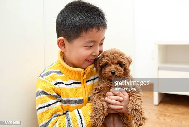 Asian boy and puppy playing in the home