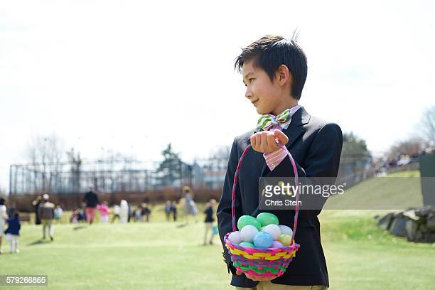 asian boy at an easter egg hunt with basket - scarsdale stock photos and pictures