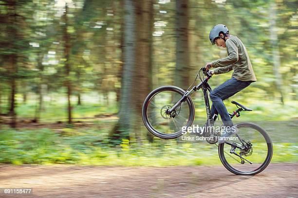 Asian boy doing a wheelie on his bike