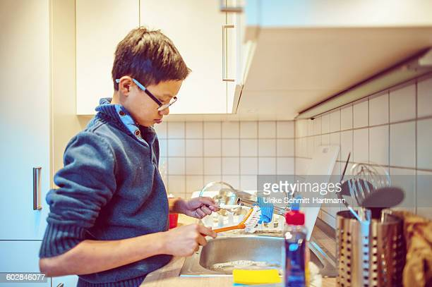 Asian boy doing wush up in small kitchen