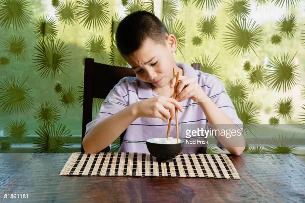 Asian boy eating bowl of rice