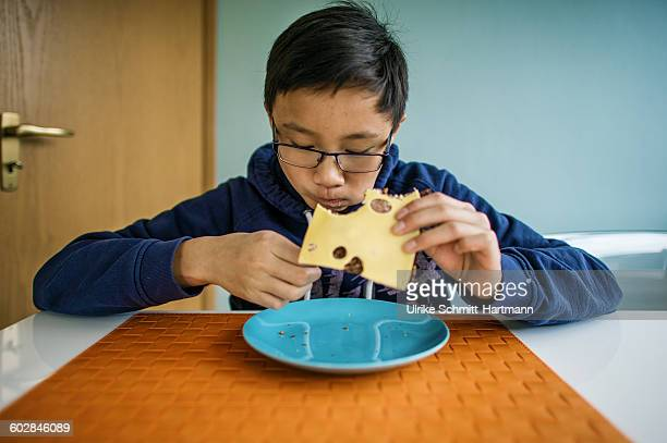 Asian boy eating bread with cheese
