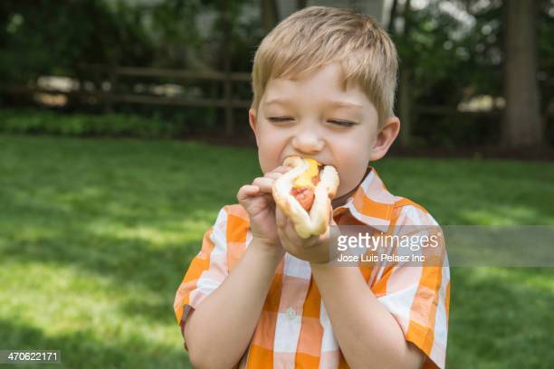 Asian boy eating hot dog