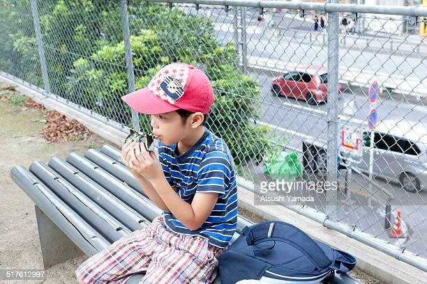 Asian boy eating rice ball in park