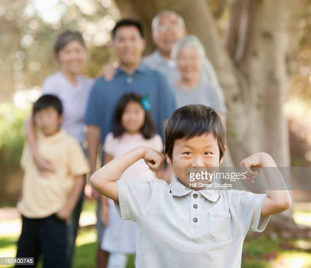 Asian boy flexing his muscles as family watches