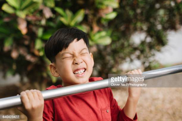 Asian boy hanging horizontal bar.