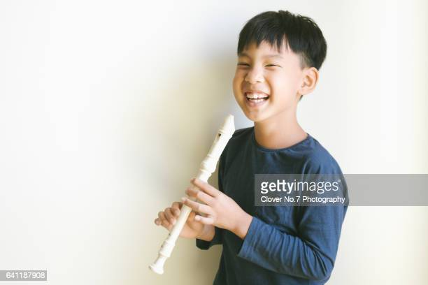 Asian boy holding a flute, happy smile.