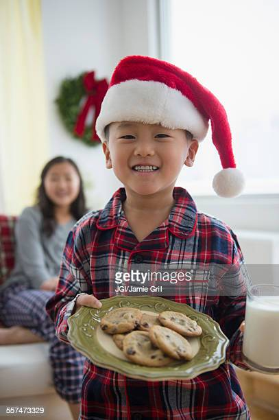 Asian boy holding plate of cookies for Santa