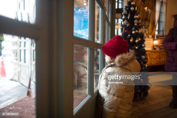 Asian boy in winter clothing looking through window.