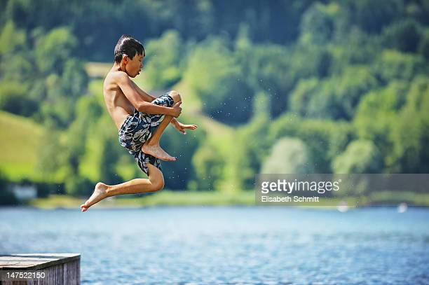 Asian boy jumping in lake