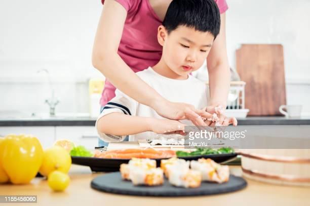 garçon asiatique apprenant à faire le rouleau de main de sushi - accompagnement photos et images de collection