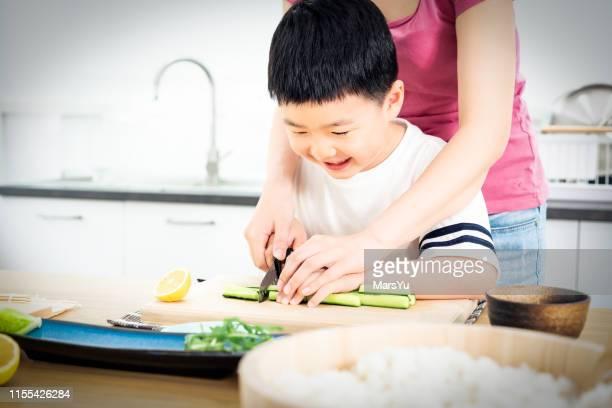 寿司ロール作りの食べ物を準備することを学ぶアジアの少年 - キッチンナイフ ストックフォトと画像