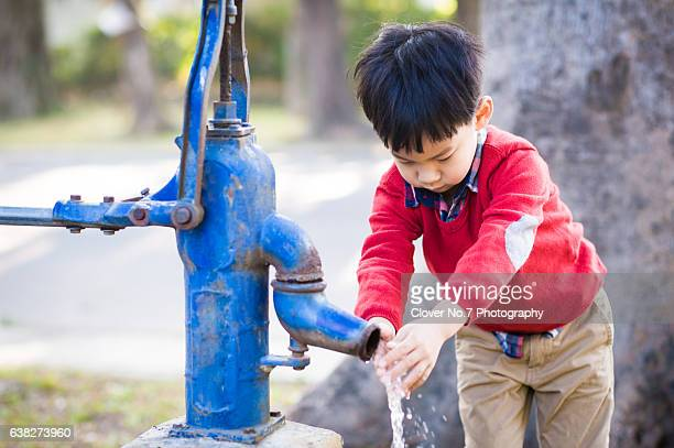 Asian boy learning to wash his hands.