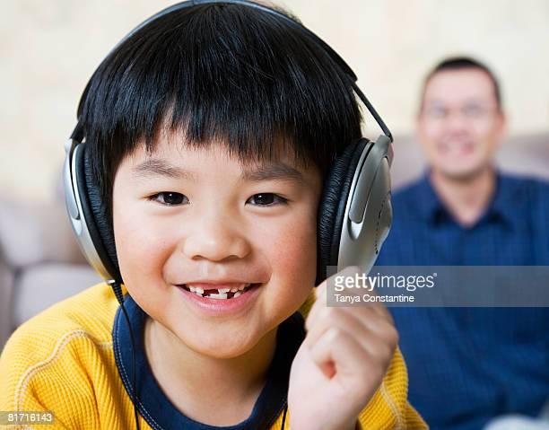 Asian boy listening to headphones