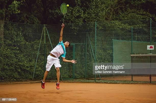 Asian boy performing a serve during a tennis match