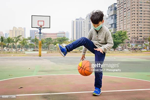 Asian boy playing basketball at a community stadium.