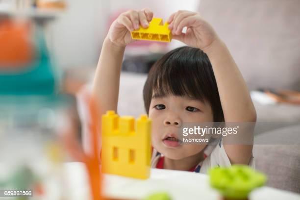 Asian boy playing building block.