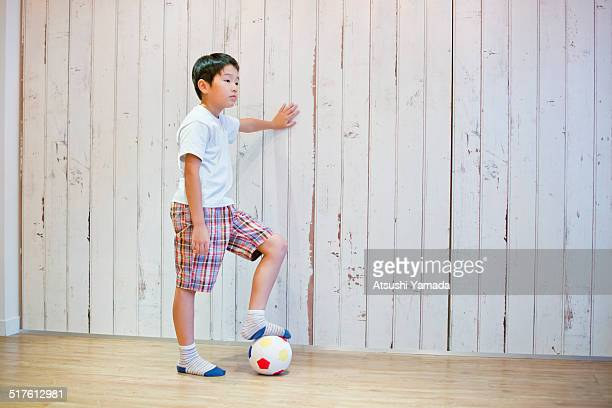 Asian boy playing with football