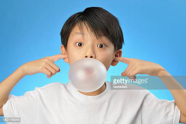 Asian boy plugging his ears and blowing a bubble