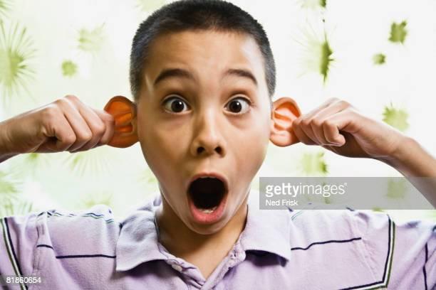 Asian boy pulling on ears