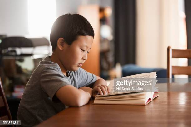 Asian boy reading book at table