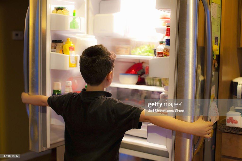 Asian boy searching through refrigerator : Stock Photo