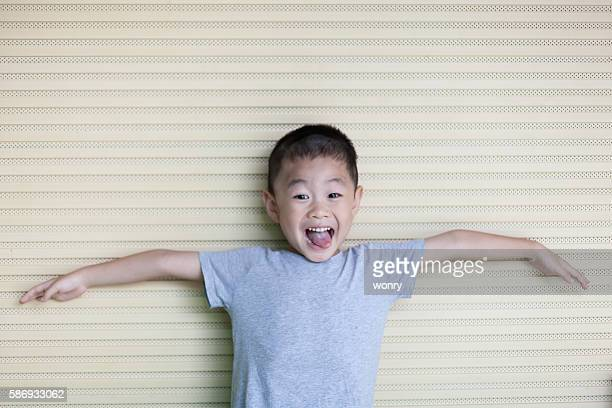 asian boy spread arms white leaning wall - gray shirt stock pictures, royalty-free photos & images