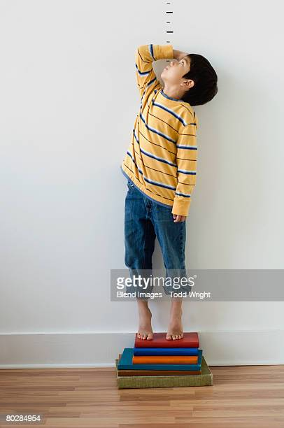 asian boy standing on books in front of height markers - tall high stock photos and pictures