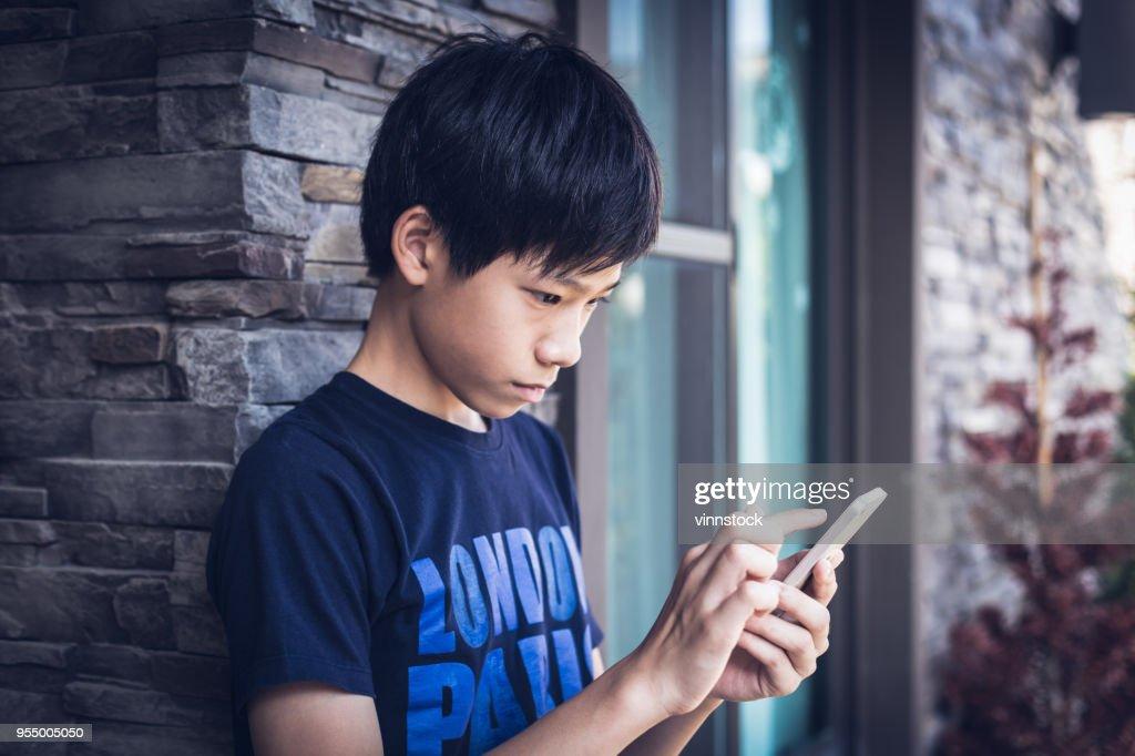 Asiatiska boy tonåring med smartphone, Utomhus sommartid. : Bildbanksbilder