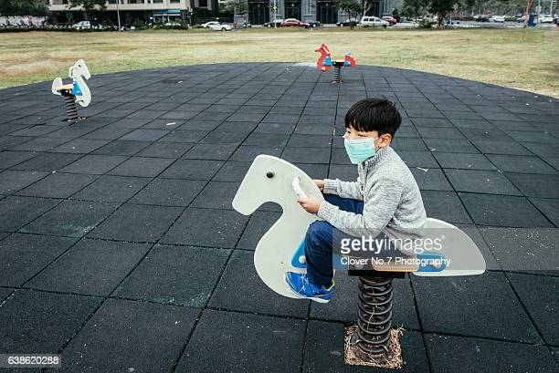 Asian boy wearing masks in the playground.