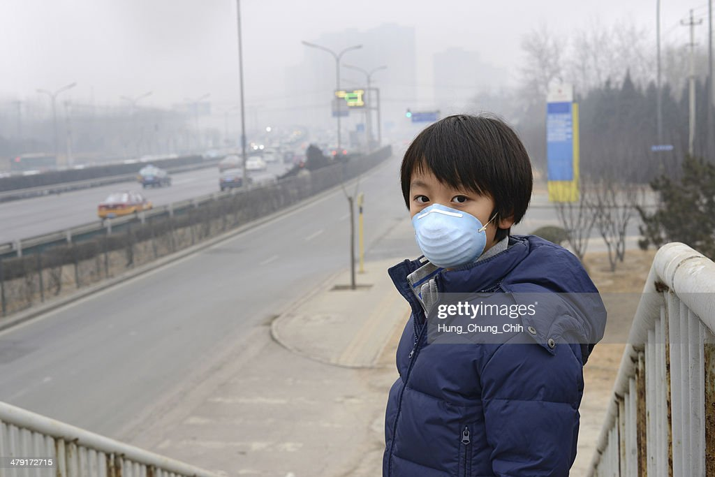 Asian boy wearing mouth mask against air pollution (Beijing) : Stock Photo