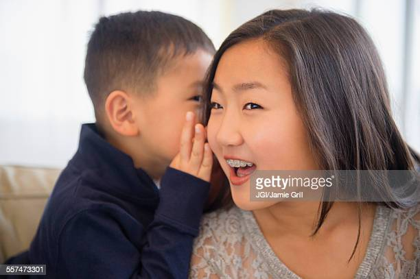 Asian boy whispering in ear of sister