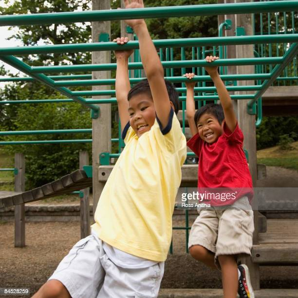 Asian boys crossing monkey bars on playground